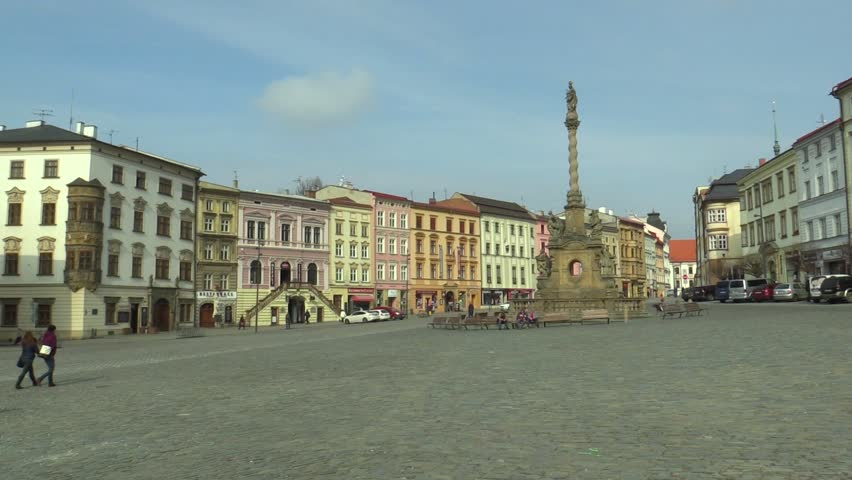 Baroque plague column called Marian on the Dolni square in the city of Olomouc. National cultural monument from 1723, architect Jan Sturmer, people walk and sit on bench, historical houses monument