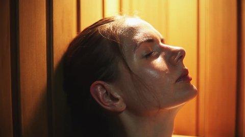 Young beautiful woman relaxing a sauna. Closeup