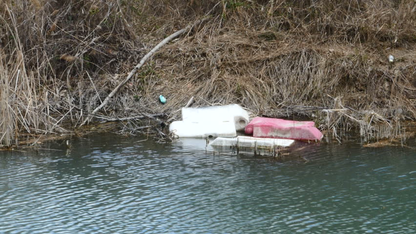 Plastic trash on the bank of a river in Madrid. Signed on April 3, 2018.   Shutterstock HD Video #1009424123