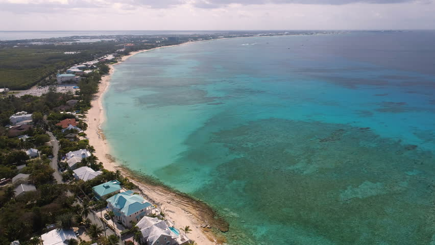 Aerial drone shot of Grand Cayman; smooth tracking shot that sees the coastline and turquoise water disappear into the Caribbean horizon