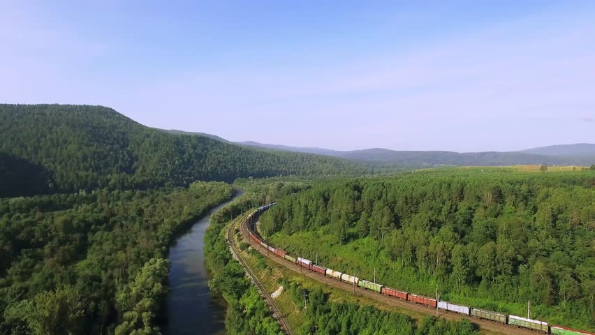 Freight train carries an electric locomotive by two-sided railway near river in the Ural Mountains - Aerial Photography, top view