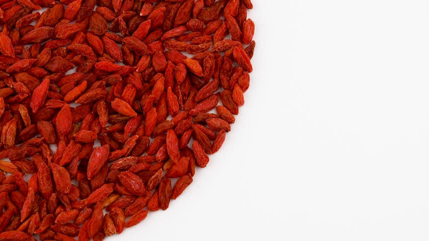 Quarter frame circle shaped heap of organic dried goji berries rotating on turn table. Isolated on white. Loopable. Close up macro. View from above/overhead.