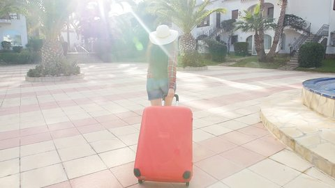 Toung woman with a red suitcase running on a resort