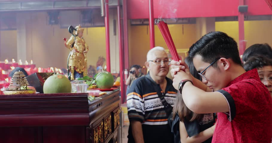 JAKARTA - Indonesia. March 28, 2018: Young Chinese man praying with incense sticks on Chinese New Year celebration at Chinese temple in Glodok, Jakarta. Shot in 4k resolution
