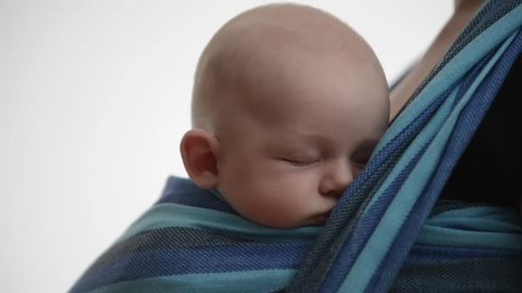 Baby smiling waking up and falling asleep in baby sling