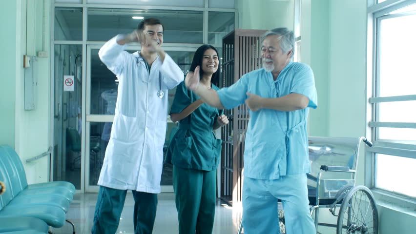 Doctor and patient dance together at hospital.
