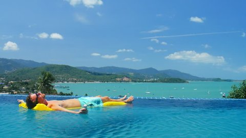 Rich man relaxing on yellow mattress in transparent water infinity pool in luxury villa with panoramic view on sea beach and flying aircraft in blue sky.
