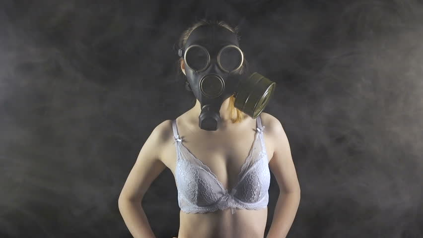 Young girl in gas mask in white lingerie