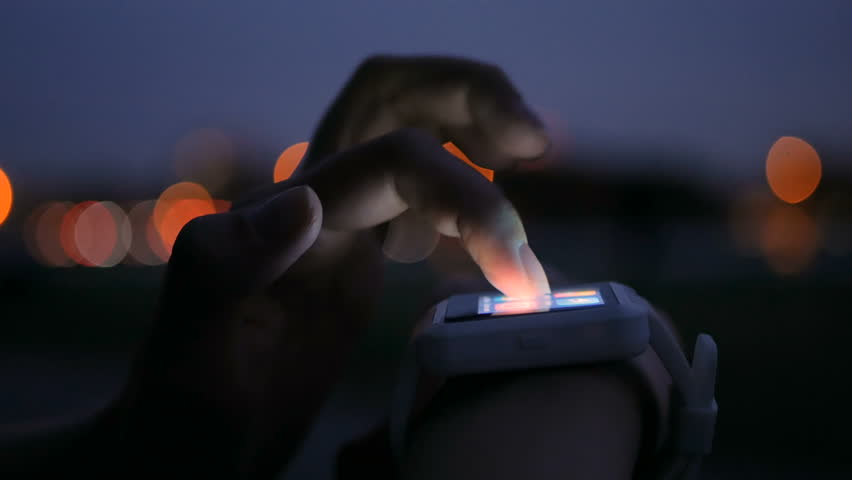 Young woman using wearable smartwatch computer device in the city - scrolling and touching. Evening time, twilight. Relax, entertainment and technology concept