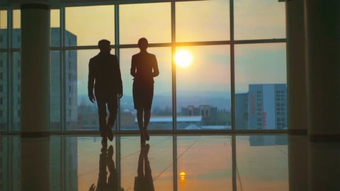 The man and woman walking in the office hall on a sunset background. slow motion