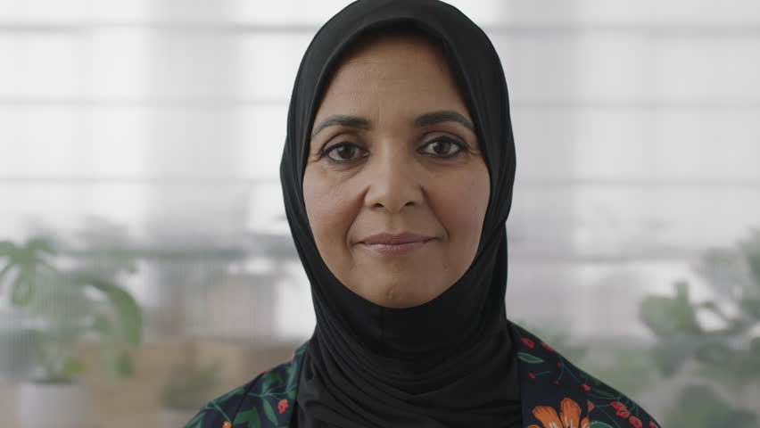 Portrait of elegant muslim business woman smiling looking happy at camera wearing traditional headscarf mature experienced female in office workspace slow motion
