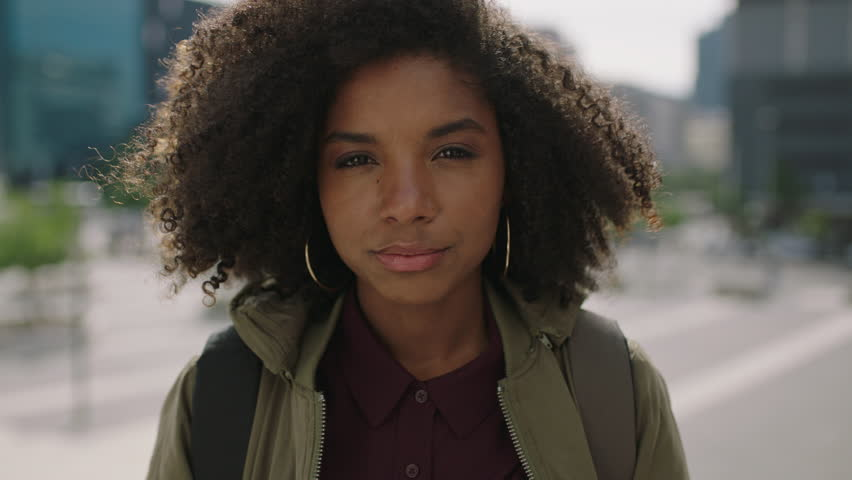 Portrait of young trendy african american woman student with afro hairstyle smiling happy enjoying urban lifestyle in city real people series   Shutterstock HD Video #1009537853