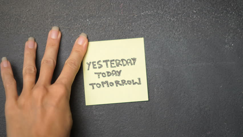 Closeup woman's hand sticking note with Yesterday, Today and Tomorrow words on the blackboard - video in slow motion