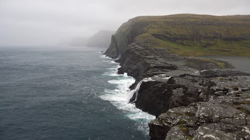 Amazing landscape of the rocky coast on Faroe Islands. Sea waves are crashing on it. Small waterfall is falling down to the sea from the cliff.