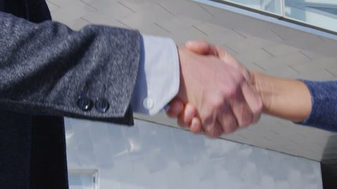 Business Handshake - business people shaking hands. Handshake between business man and woman outdoors by business building. Casual wear, young people in their 30s. shaking hands close up. SLOW MOTION