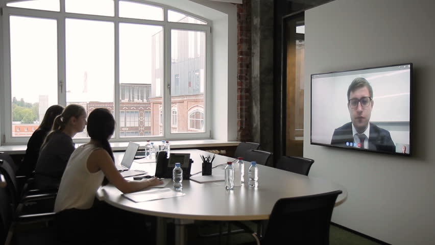 Employees hold meeting through video conferencing on plasma. Three women sit at table with large monitor, through which they communicate with manager in business suit and glasses.