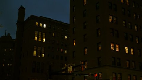 Camera pans up a a brick apartment building in the city at night
