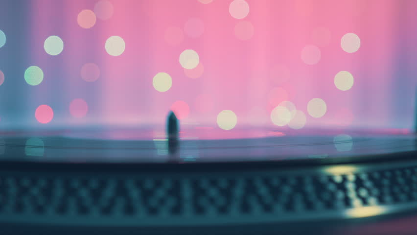 The moment of a rotating vinyl plate turntable on a pink background and bright bokeh lights. Sound technology for DJ to mix and play music. The man's hand puts and removes needle from the vinyl plate