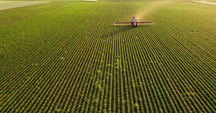 Aerial drone shot of a farmer spraying soybean fields #1009627403