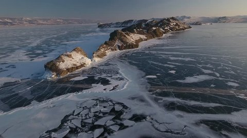 Great height forward fast texture blue ice cracked field spacious surface Lake Baikal Russia Olkhon Sight. Rock mountain snow drifts. Innocent wild coastal. Winter sunrise. Aerial Drone Top