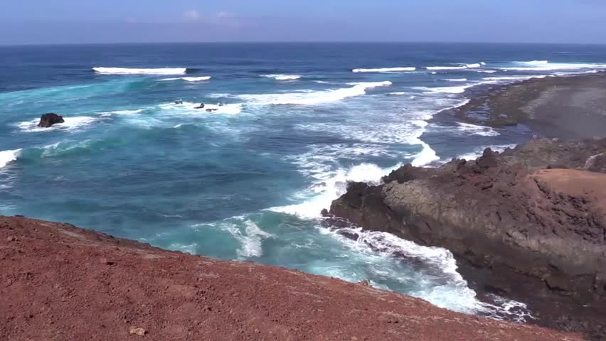 Panoramic view from the splendid waves of the Atlantic ocean to the small village of El Golfo in Lanzarote - 1080p