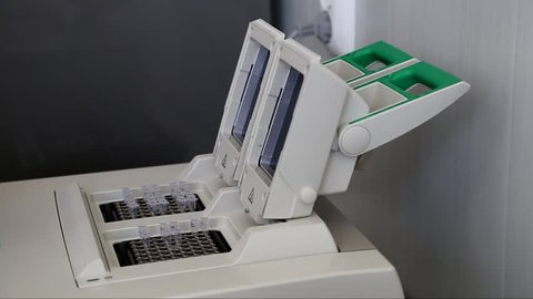 Scientist with gloved hand putting DNA sample into real-time PCR-cycler