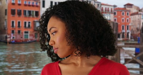 Somber looking black female looking away from camera while in Venice, Italy. Thoughtful African-American female looking off-screen by Grand Canal in Venice. 4k