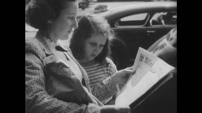 1940s: Woman and girl look at newspaper. View of newspaper over woman's shoulder. View of sign, tilt up to window, man behind window opens blinds. Man talks to boys, boys exit.