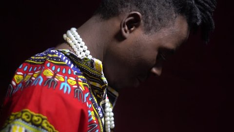 A man from Angola in traditional dashiki clothes puts a bright kerchief on his shoulders, bit slow motion