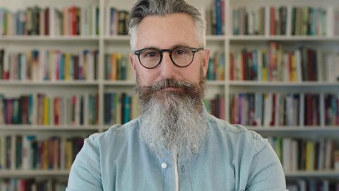portrait of mature caucasian professor with beard smiling happy at camera in library bookshelf background wearing glasses real people series