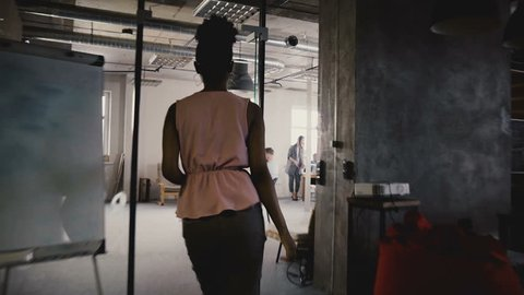 Camera follows happy black female leader enter office, talk to colleagues. Multiethnic colleagues in modern coworking 4K