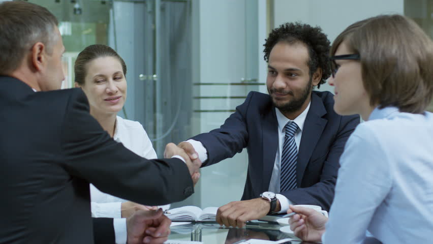PAN shot of two experienced businessmen shaking hands and speaking with female colleagues at corporate meeting | Shutterstock HD Video #1009705013