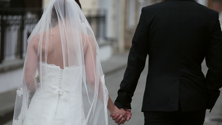 A beautiful married couple walking down the park and holding their hands.  Wedding dress. Green trees and a building on the background. | Shutterstock HD Video #1009708673