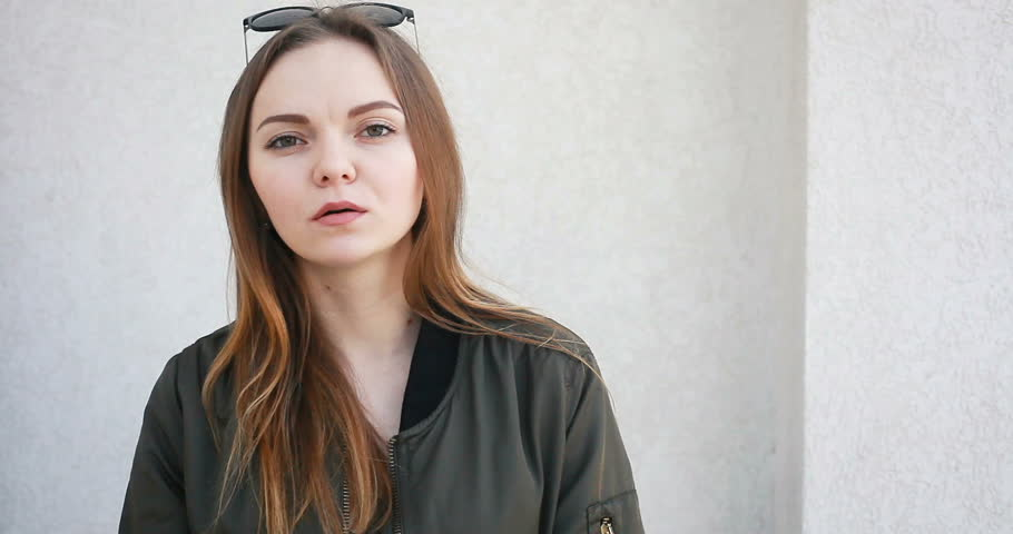 People, health, 4K, dentist and lifestyle concept - Outdoor portrait of young attractive female in stylish outfit chewing gum, smiling and looking camera. Portrait of hipster girl blowing bubble gum | Shutterstock HD Video #1009712303