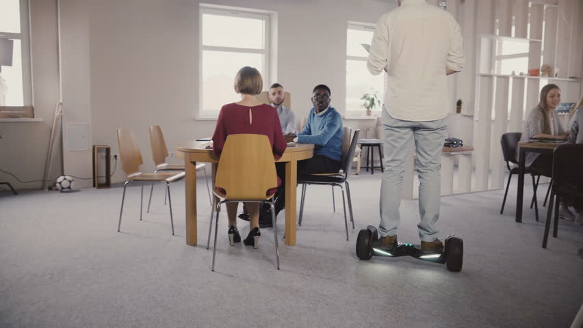 Young male boss using hoverboard to come and talk to colleagues. Confident leader uses technology in modern office 4K. | Shutterstock HD Video #1009717133