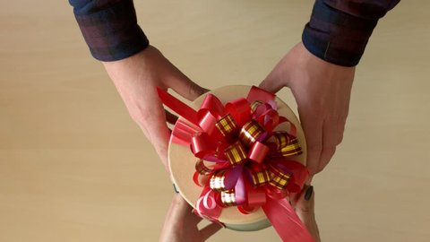 Men's hands give a box with a gift to a woman. Top view.