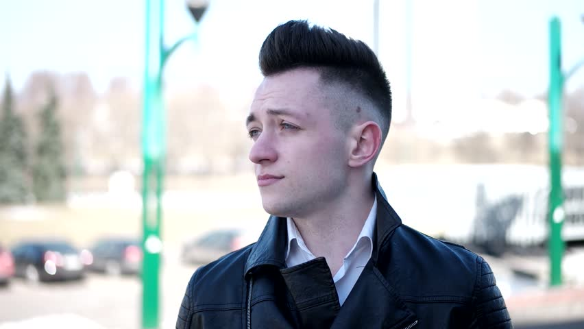 A young guy dressed in a leather jacket. The guy with the fashion hair. The guy is in the center of the city and with an astute look. Steady look. A European guy at the age of 20 | Shutterstock HD Video #1009742243