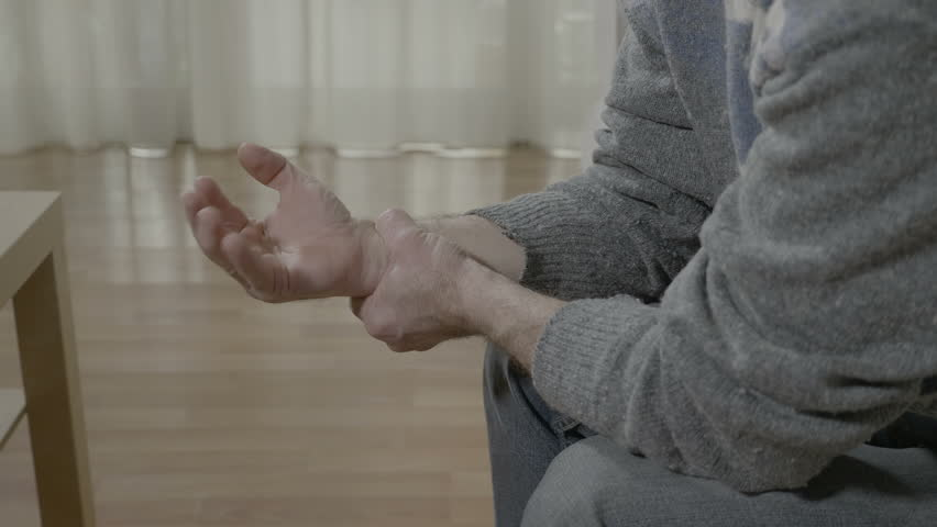 Closeup of old man with arthritis touching his painful wrist having rheumatism sitting on the couch at home | Shutterstock HD Video #1009746413