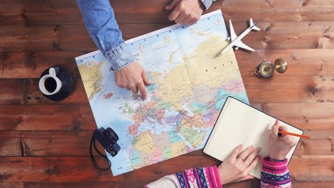 couple planning travel vacation on world map top view