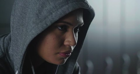 Close up of a beautiful fit young woman (girl) with a gray hooded sweatshirt in the gym's locker room, getting ready to train