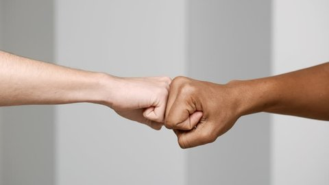 Hands gesture of two multiethnic men bumping fists closeup, isolated over white background in slow motion, friendship and greeting concept