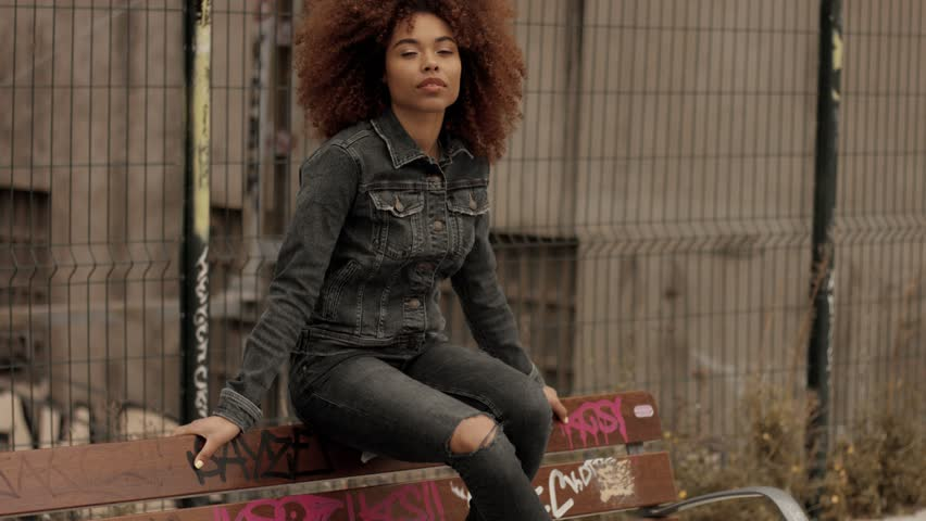 Black mixed race woman with big afro curly hair sits on bench with graffity | Shutterstock HD Video #1009812413