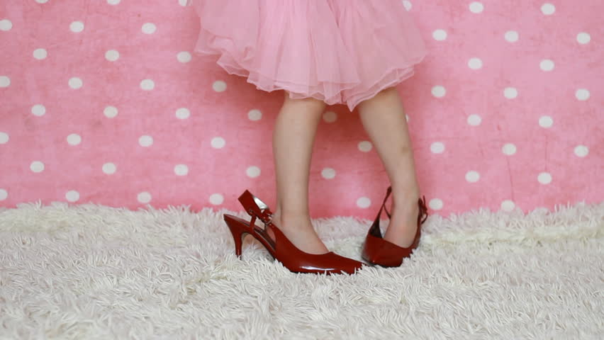 Glamour . Fashion. Beauty. A child dresses adult shoes on a pink background. Girl fashionista. Baby legs in mother's shoe with heel.
