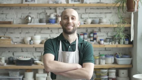 Portrait of male ceramist, who is standing in his studio and watching to the camera, slow motion. Young man in green polo t-shirt and white dickey has beard and smiling. Wooden shelves with colours