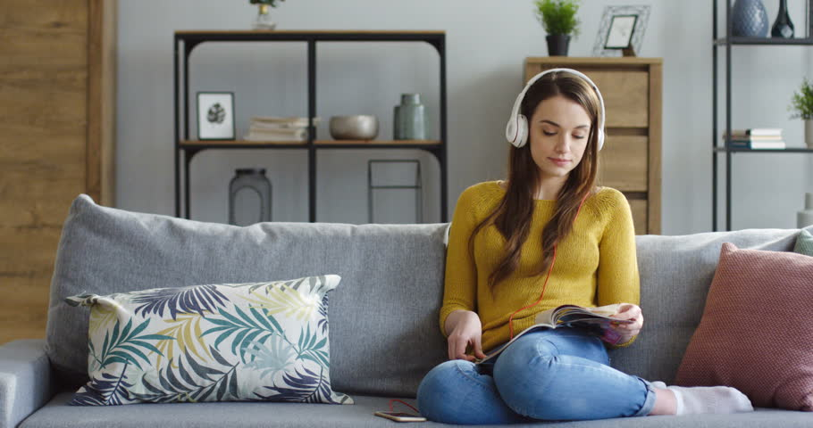 Young pretty woman in the headphones sitting on the gray sofa with a smartphone in hands and listening to the music in the nice living room. Indoors | Shutterstock HD Video #1009826633