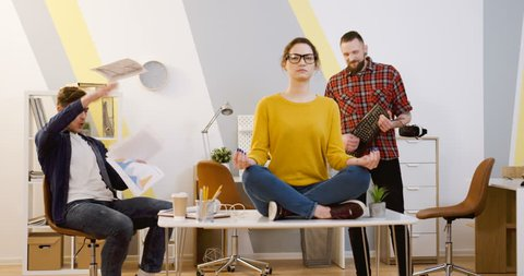 Chaos in the office during the workday. Female office worker in glasses meditating on the desk in the lotos pose while her male co-workers imitating play musical instruments, dancing and having fun in