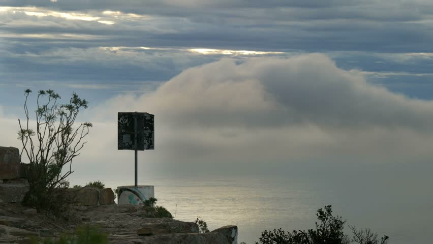 Trig point on rocky platform at Kloof Corner, Table Mountain hiking trail, with plants silhouetted against Atlantic Ocean sun lit surface with Cold frontal system fog & cloud banks moving.