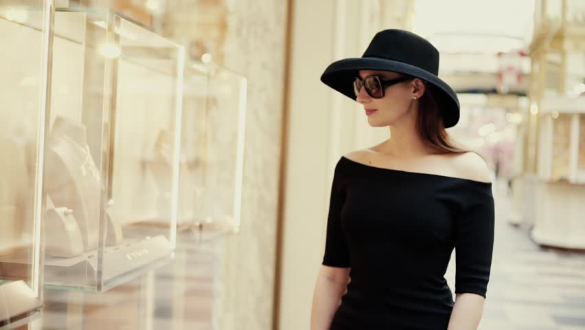A beautiful stylish lady in a hat and sunglasses approaches the shop window of a boutique and looks at the goods with interest. Luxury jewelry store | Shutterstock HD Video #1009843763