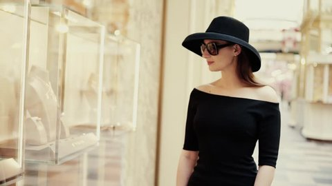 A beautiful stylish lady in a hat and sunglasses approaches the shop window of a boutique and looks at the goods with interest. Luxury jewelry store