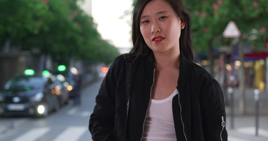 Chinese woman in black bomber jacket on city street with hair blowing in wind. Asian millennial tourist waits on sidewalk with pockets in Paris. 4k